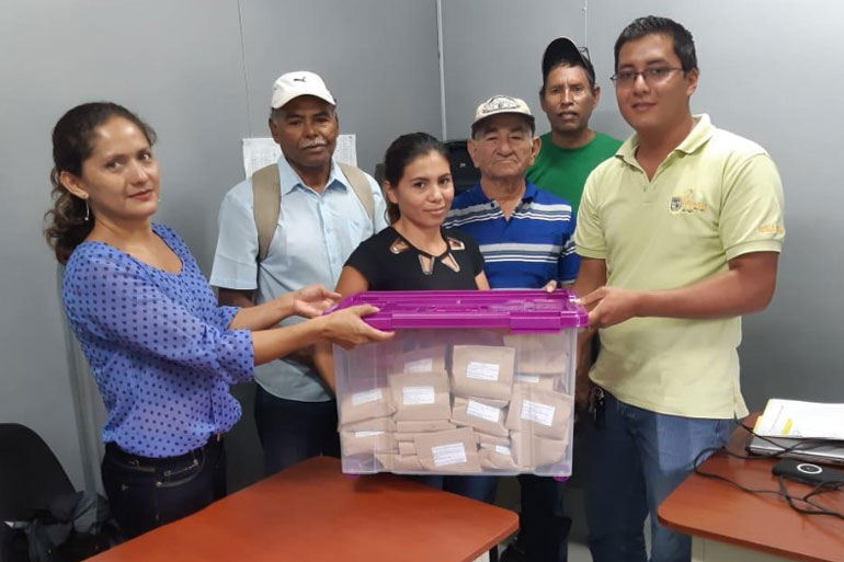 Six happy people hold a large plastic packing see-through container that holds many brown paper packages